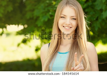 Summer girl portrait.  Closeup of a woman smiling happy on sunny summer or spring day outside in park showing victory or peace sign. Pretty young woman outdoors.