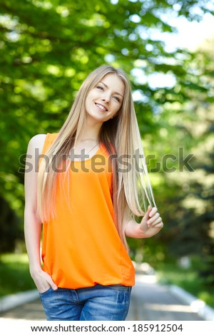 Summer girl portrait.  Playful casual woman standing with hand in pockets smiling happy on sunny summer or spring day outside in park. Pretty young woman outdoors. - stock photo