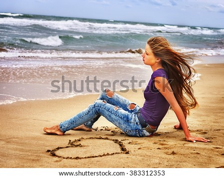 Summer girl sea.  Teenager draws heart on sand and  looks into the distance