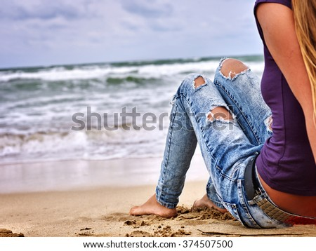 Summer girl sea.  Woman wearing in jeans with holes sitting on coast near ocean with waves. Hot dog leg selfie.  - stock photo