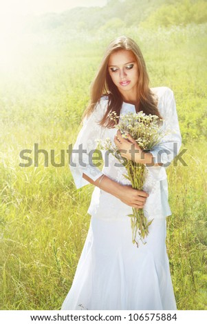 Summer girl with chamomile bouquet - stock photo