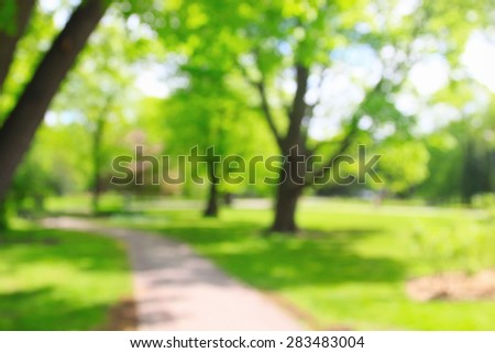 Summer growing sunny park with unrecognizable people - stock photo