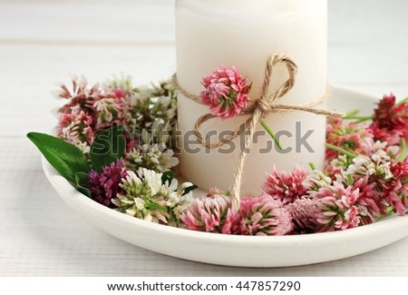 Summer handmade simple candlestick decor. Candle and fresh meadow clover flowers on plate.  - stock photo