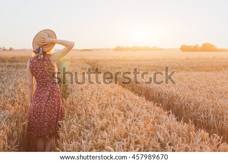 summer happy young woman in wheat field by sunset, daydream, beautiful background with place for text - stock photo