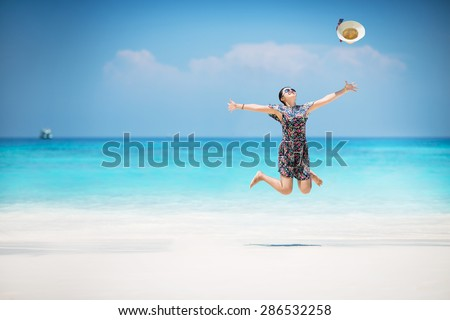 Summer happy young woman jumping in sea on the beach. - stock photo