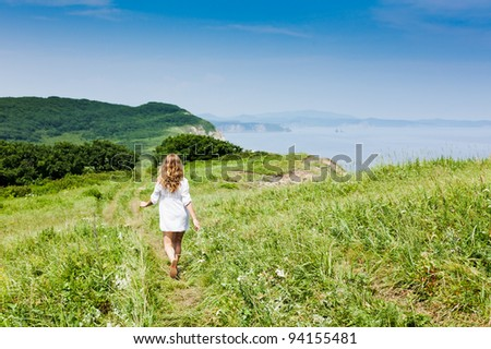 Summer harmony - A blond-haired girl walking on a grassy track along a seaside towards a green hill, backshot. Lots of copy space and room for text