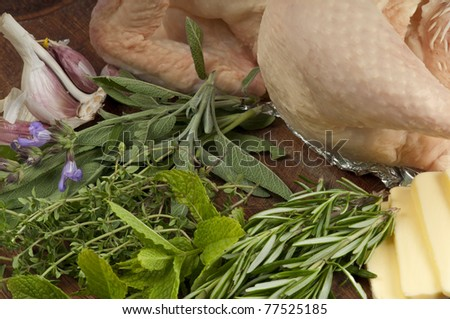Summer herb chicken ingredients.  Raw chicken and butter with fresh, rosemary, thyme, mint, sage and garlic  ready to be chopped and mixed together.
