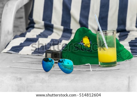 Summer holiday abstract with a green hat, blue sunglases and orange juice lying on a black-white beach chair, just like dreaming of a summer holiday.