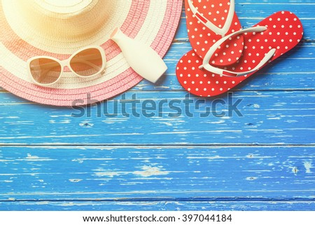 Summer holiday background, Beach accessories on white wood table, Vacation and travel items, Red flip flop with sunglasses, moisturizer and summer beach hat on wood table - stock photo