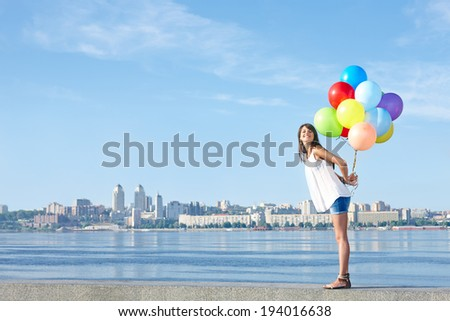 Summer holiday, celebration and present concept: happy young woman holding colorful balloons behind back, standing in full length, city view, outdoors - stock photo