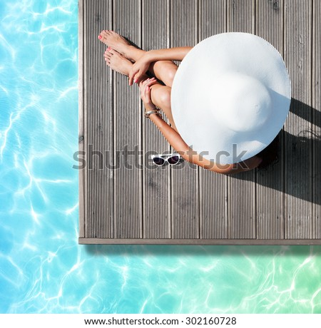 Summer holiday fashion concept - tanning woman wearing sun hat at the pool on a wooden pier view from above - stock photo