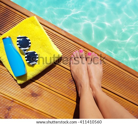 Summer holiday fashion selfie concept - woman on a wooden pier at the pool with summer accessories; sunglasses, towel and sunscreen - stock photo
