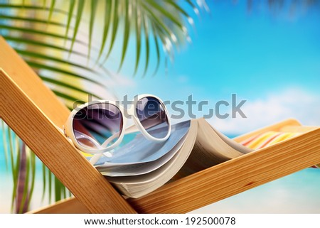 Summer holiday setting with book on beach chair  - stock photo