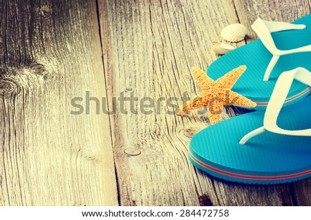 Summer holiday setting with flip flops and sea shells - stock photo