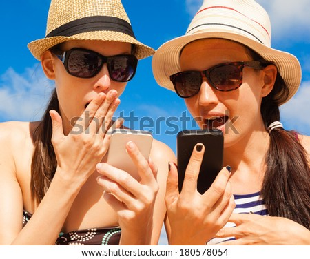 Summer holiday, technology and beach concept. Girls using smart phone on the beach. - stock photo