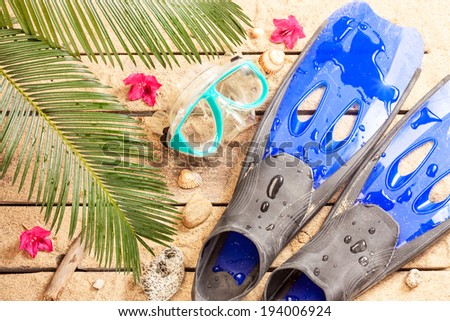 Summer holiday (vacation) tropical beach - palm tree leaves, exotic flowers, wet fins and goggles on sand. Diving equipment from above. - stock photo