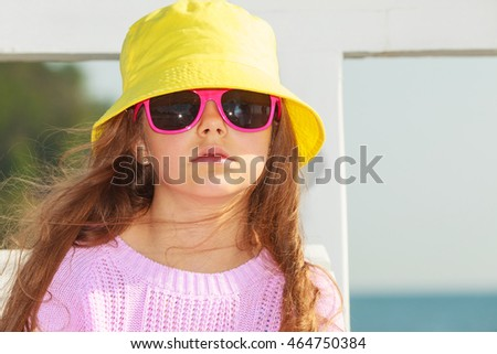 Summer holidays and leisure. Young little girl tourist in yellow cap outdoors. Child waiting for parent on seaside beach.