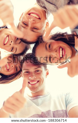 summer holidays and teenage concept - group of smiling teenagers looking down and showing thumbs up - stock photo