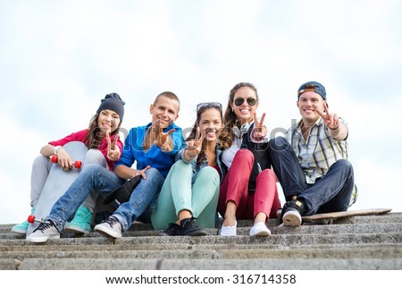 summer holidays and teenage concept - group of teenagers showing finger five gesture - stock photo