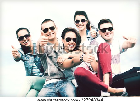 summer holidays and teenage concept - group of teenagers showing thumbs up outside - stock photo