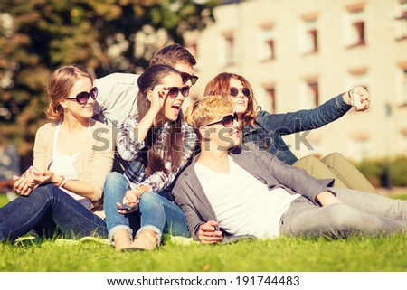 summer holidays and teenage concept - group of teenagers taking selfie in park with smartphone