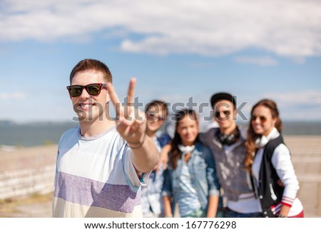 summer holidays and teenage concept - teenage boy in sunglasses hanging out with friends outside - stock photo