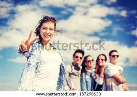 summer holidays and teenage concept - teenage girl in sunglasses hanging out with friends outside and showing thumbs up - stock photo