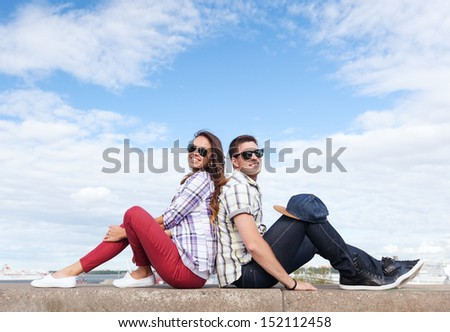 summer holidays and teenage concept - teenagers sitting back to back - stock photo
