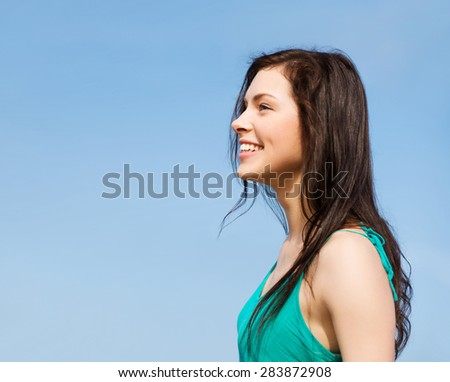 summer holidays and vacation - beautiful smiling girl over blue sky