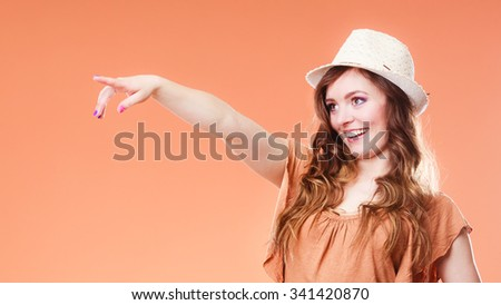 Summer holidays and vacation. Girl in fashionable clothes straw hat holding bag handbag. attractive woman tourist pointing copy space with finger on brown - stock photo