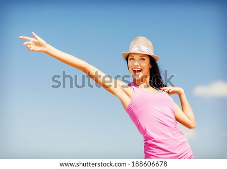 summer holidays and vacation - girl in hat showing direction on the beach - stock photo