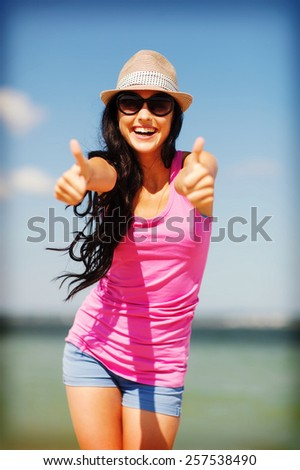 summer holidays and vacation - girl showing thumbs up on the beach - stock photo
