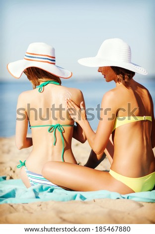 summer holidays and vacation - girls applying sun protection cream on the beach - stock photo