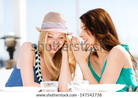 summer holidays and vacation - girls gossiping in cafe on the beach - stock photo