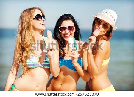 summer holidays and vacation - girls in bikini with ice cream on the beach - stock photo