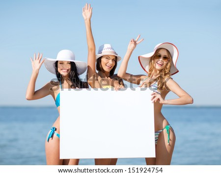 summer holidays and vacation - girls in bikinis holding blank white board on the beach - stock photo
