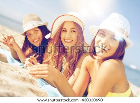 summer holidays and vacation - girls in bikinis sunbathing on the beach - stock photo