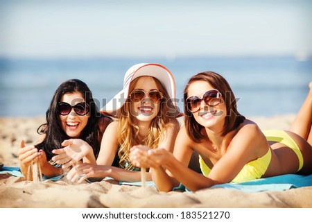summer holidays and vacation - girls sunbathing on the beach - stock photo