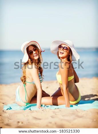 summer holidays and vacation - girls sunbathing on the beach - stock photo