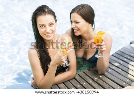 Summer holidays and vacation - girls sunbathing on the pool