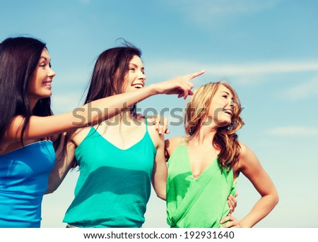 summer holidays and vacation - girls walking on the beach and showing direction - stock photo