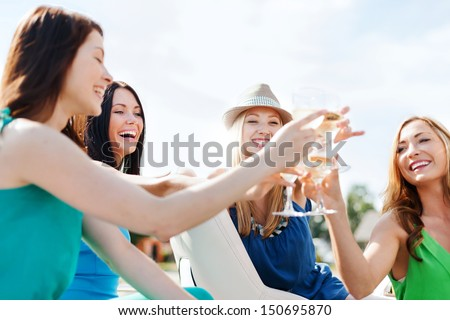 summer holidays and vacation - girls with champagne glasses on boat or yacht - stock photo