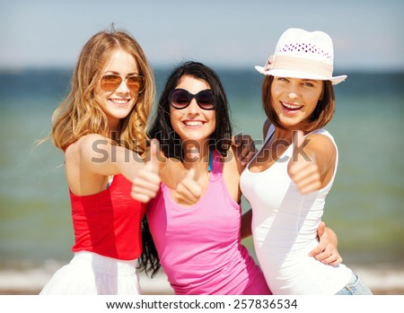 summer holidays and vacation - group of girls showing thumbs up on the beach - stock photo