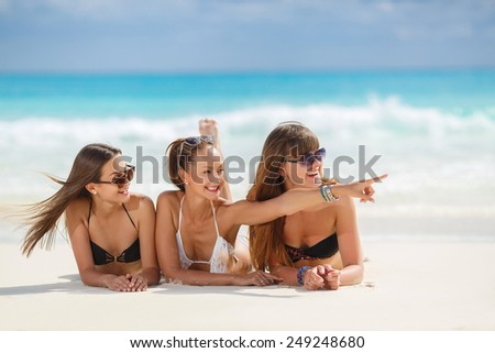 summer holidays, beach concept - girls having fun on the beach. group of friends at the beach. summer holidays and vacation - girls in bikinis sunbathing on the beach - stock photo