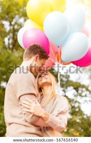 summer holidays, celebration and dating concept - smiling couple with colorful balloons in the park - stock photo