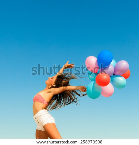 Summer holidays, celebration and happiness concept - attractive athletic woman teen girl jumping with colorful balloons hair blowing on wind outdoors sunny day, blue sky background - stock photo