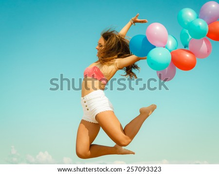 Summer holidays, celebration and lifestyle concept - beautiful woman teen girl jumping with colorful balloons outside on beach