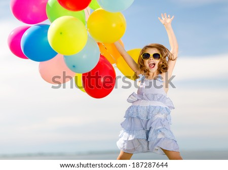 summer holidays, celebration, children and people concept - happy jumping girl with colorful balloons outdoors - stock photo