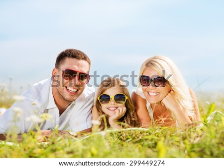 summer holidays, children and people concept - happy family with blue sky and green grass - stock photo