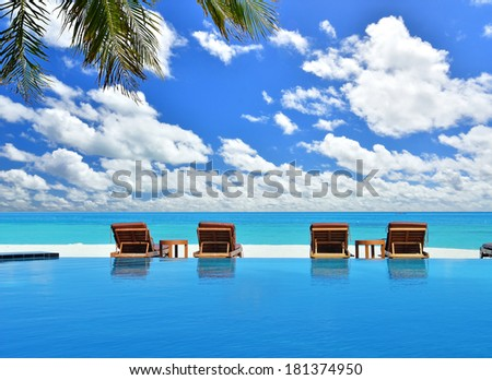 Summer holidays concept --  Sunbeds beside swimming pool in tropical beach resorts - stock photo